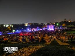 Picture of night time at Bear Creek Folk Festival. People are outside on a hill. There are bright lights in the background.
