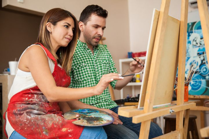 Couple painting together on canvas for date night in grande prairie