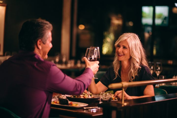 Couple toasting to each other in dark lit restaurant for date night in grande prairie