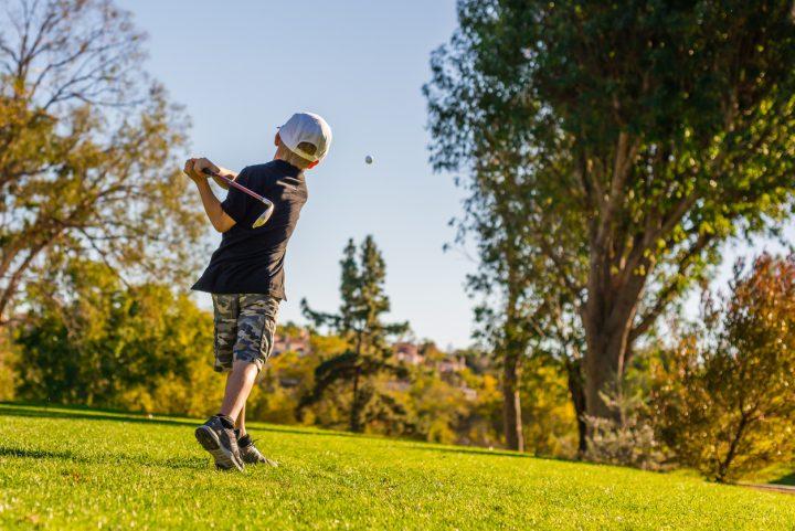 south bear creek - little boy golfer teeing off on a sunny day