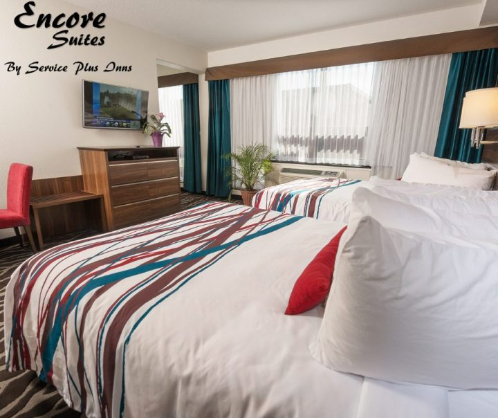 Encore Suites - image of two hotel beds with desk and TV