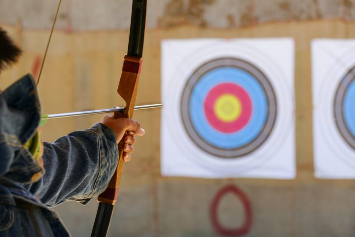 person aiming bow and arrow at target