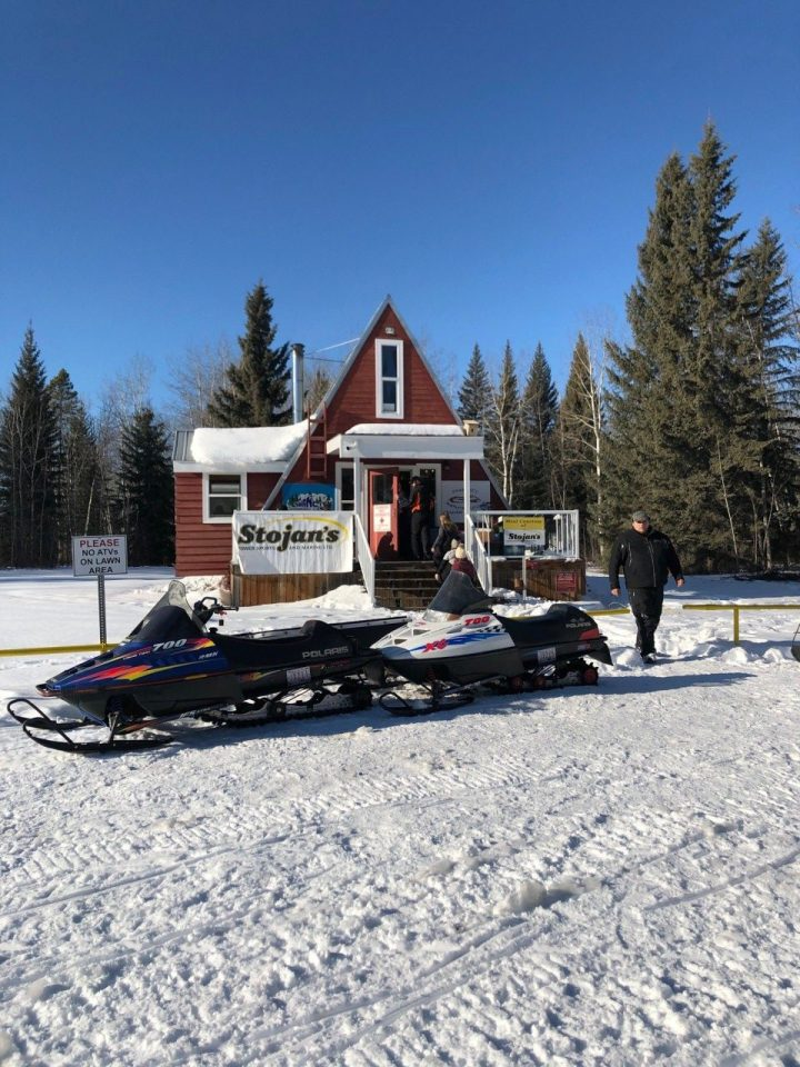 two snowmobiles with man outside storjan's - guide to snowmobiling