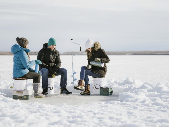 3 persons sitting on a frozen lake going ice fishing