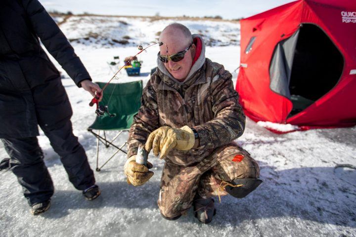 man baiting ice fishing rod
