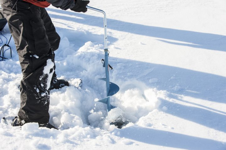 person using ice auger going ice fishing in grande prairie region