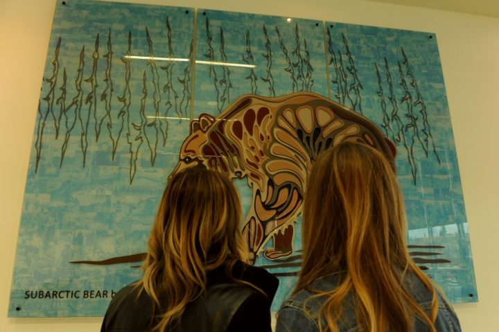two people looking at an art piece in gallery