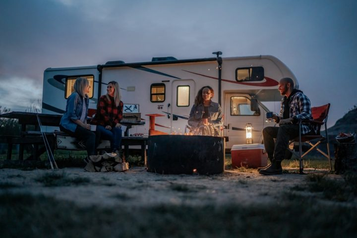 three friends sitting around a fire and an RV