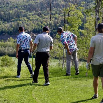 Men golfing overlooking a river at River Stone Golf Course.
