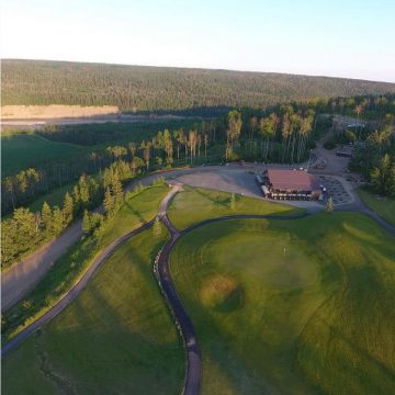 Skyview of golf green and clubhouse at Riverstone Golf Course.