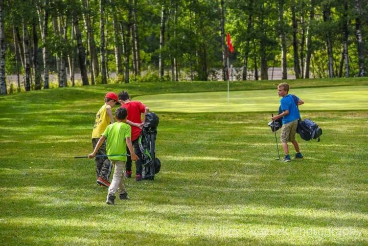 three kids carrying golf bags on golf course
