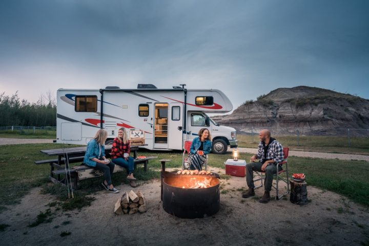 four people sitting around a fire camping by an RV - spring in grande prairie