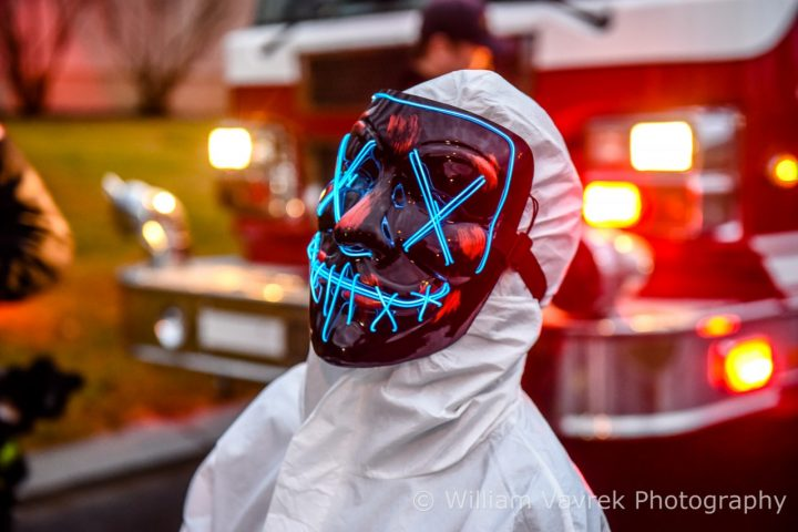 Grande Prairie resident dressed up with LED Halloween mask in front of a fire truck.
