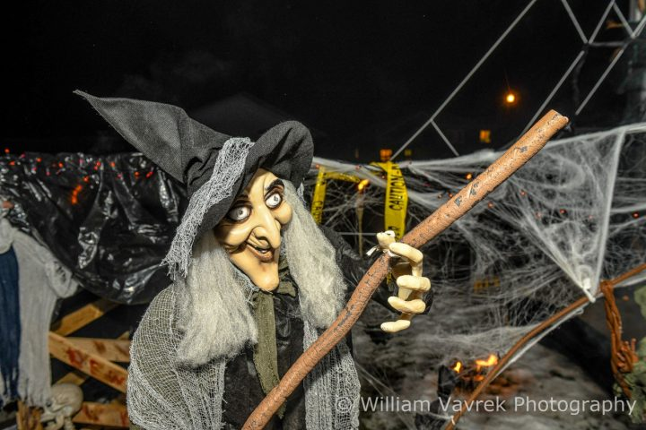 Witch and broom Halloween display at a Grande Prairie Tourism event with cobwebs and caution tape in the background.