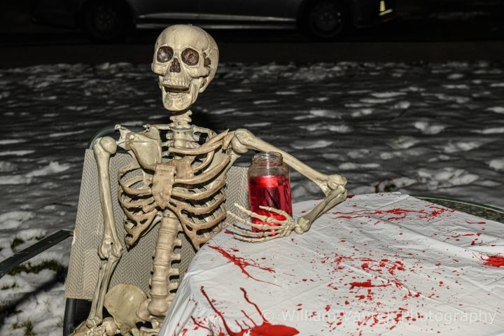 Spooky skeleton sitting with a glass of Halloween punch at a Grande Prairie Tourism event table splattered with fake blood.